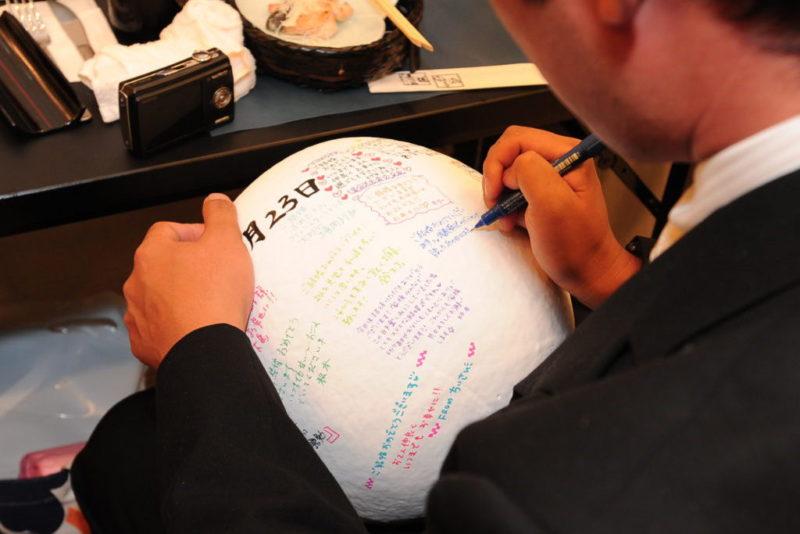 寿だるまの背面に祝福のメッセージを書く男性ゲスト