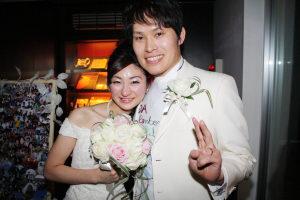 結婚式二次会後にピースで写真を撮る新郎新婦