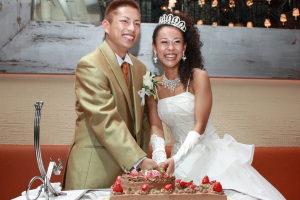 満面の笑顔でケーキ入刀する新郎新婦