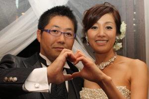 結婚式二次会後にハートマークを作って笑顔の新郎新婦