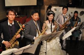 サックスを吹く前に笑顔の新郎新婦とゲスト演奏者