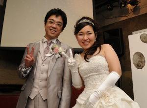 結婚式二次会後に笑顔でピースの新郎新婦