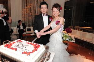 カメラ目線でケーキ入刀する新郎新婦