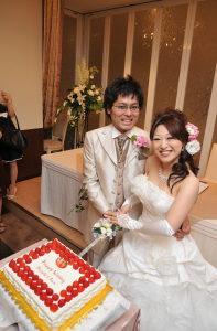 満面の笑みでケーキ入刀する新郎新婦