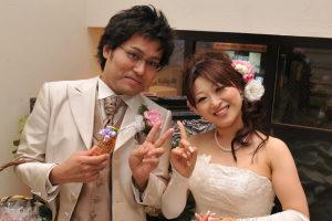 結婚式二次会の後に笑顔でピースする新郎新婦