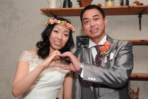 結婚式二次会の後に笑顔でハートマークを作る新郎新婦