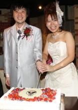 卓球をモチーフにしたウェディングケーキに入刀する新郎新婦