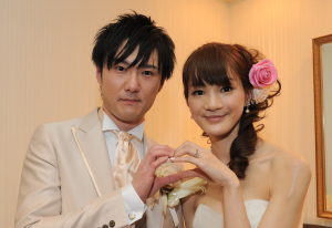 結婚式二次会後に笑顔でハートマークを作る新郎新婦