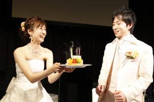 誕生日ケーキのケーキを笑顔で新郎に渡す新婦
