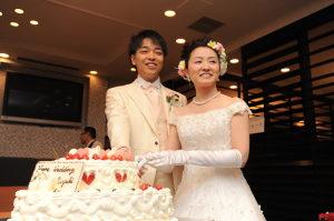 笑顔でケーキ入刀する新郎新婦