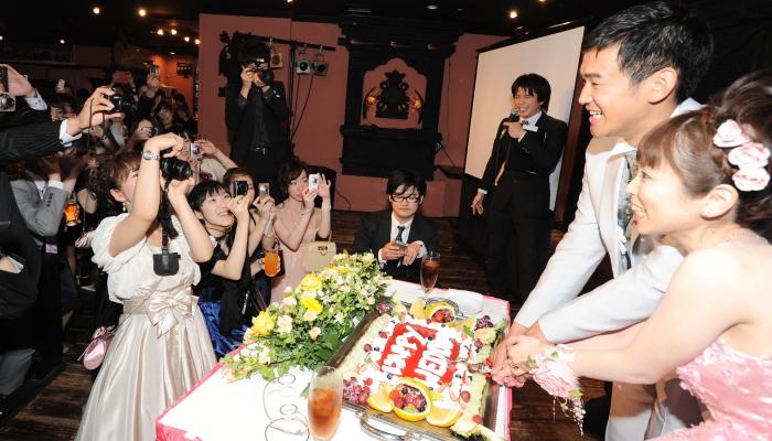 大勢のゲストにカメラを向けられてケーキ入刀